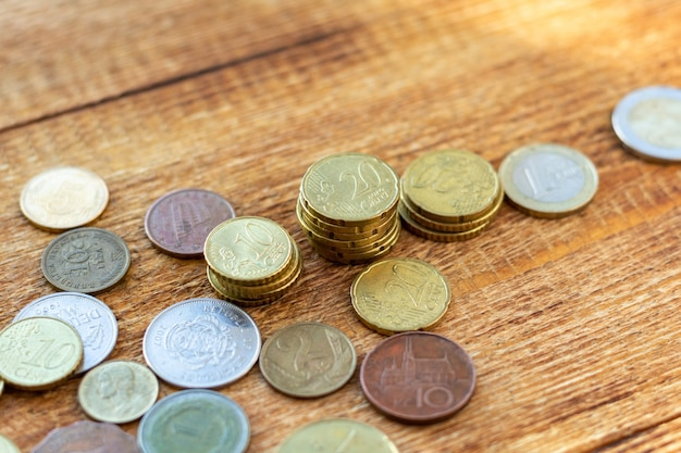 Coins old rusty brass euro seychelles bulgaria china germany pile pack heap stack on a wooden background finance economy investment savings concept mock up selective focus close up