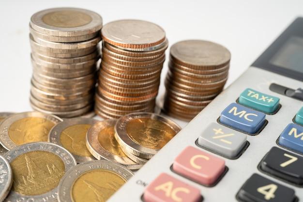 계산기와 그래프 용지에 동전. 금융 개발, 은행 계좌, 통계, 투자 분석 연구 데이터 경제, 증권 거래소 거래, 비즈니스 회사 개념.