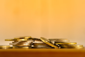 Coins on one another in a pile of on the table. Light background