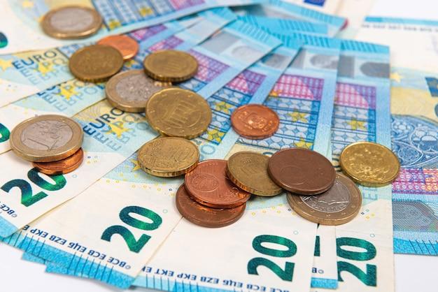 Монеты на фоне банкнот двадцать евро, крупным планом