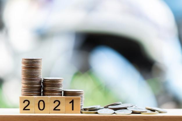 Монеты на деревянном столе, как растущий граф. с текстом 2021 года на зеленом размытом фоне боке.