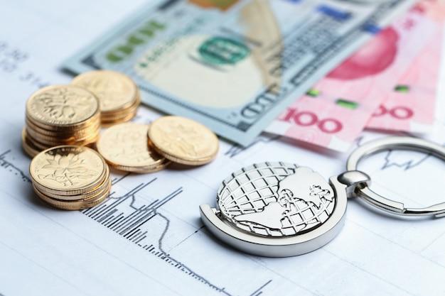 Monete, soldi di carta e globo su bianco sfondo di forma statistica