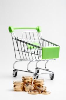 Coins куча и корзина для покупок на белом фоне