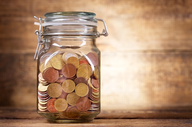 Coins for savings in the glass jar on wooden background