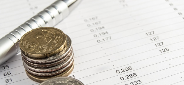 Coins and silver pen lying on financial documents, accounting and statistics concept, top view, banner
