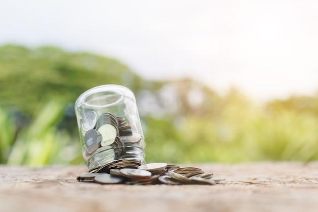 Монеты пролились из стеклянной банки на фоне природы размытия стола, сохраняя на будущее, инвестиционную бизнес-концепцию.