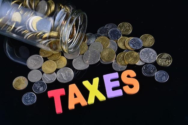 Монеты выливаются из банки с деньгами со словом налоги