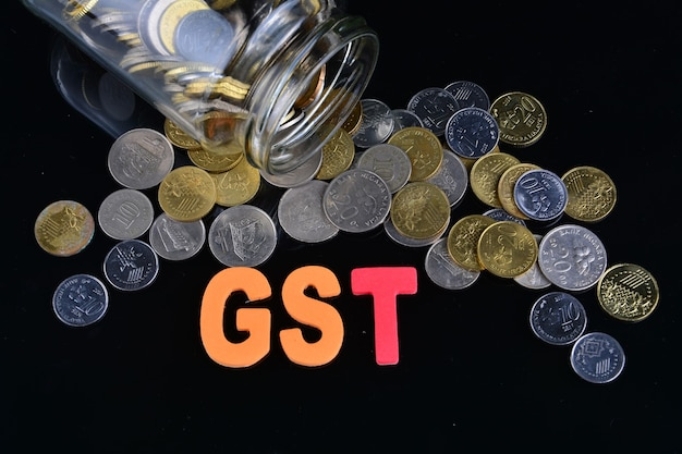 Coins spilling from a money jar with word gst