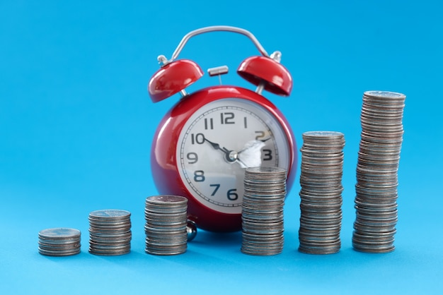 Coins stacked in ascending order standing against background of alarm clock