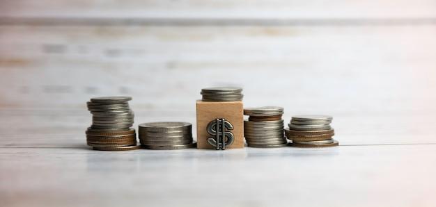 Монеты сложены рядом с деревянным блоком на деревянной доске