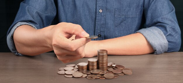Coins stacked on each other in different positions. hand in business casual money