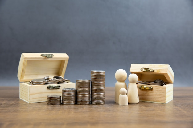 Coins stacked in a graph shape with family wooden doll.