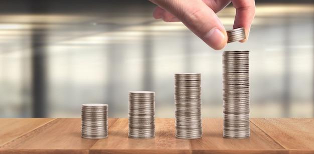 동전은 서로 다른 위치에 쌓여 있습니다. 비즈니스 캐주얼 돈을 손에 동전
