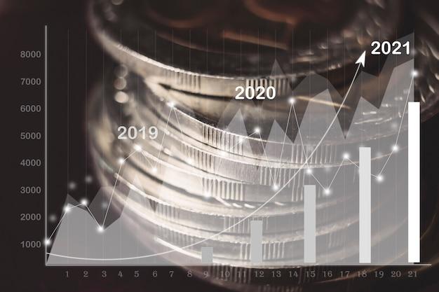 어두운 배경에서 서로 다른 위치에 동전이 쌓여 있습니다. 2021년 실적 차트입니다.