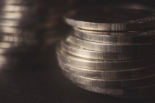 어두운 배경에서 서로 다른 위치에 동전이 쌓여 있습니다. 돈 개념입니다. 확대. 돈과 절약 개념입니다. 성공, 부와 빈곤, 빈곤 개념. 비즈니스 성장 개념입니다.