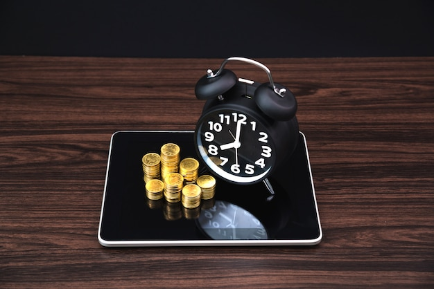 Coins stacks and alarm clock on tablet