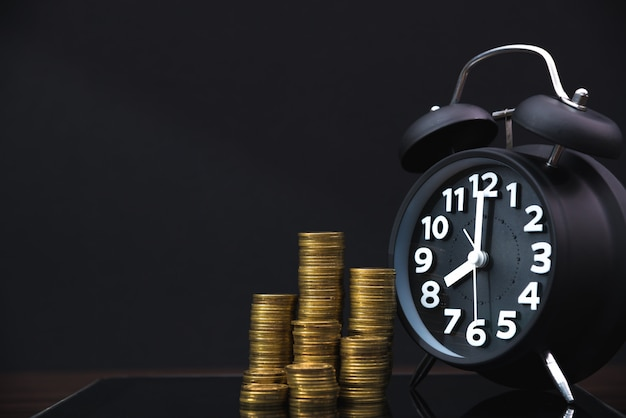 Coins stacks and alarm clock with table