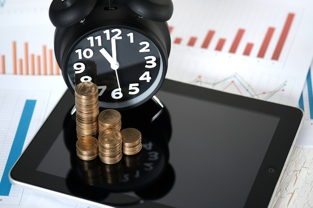 Coins stacks and alarm clock with tablet and financial graph