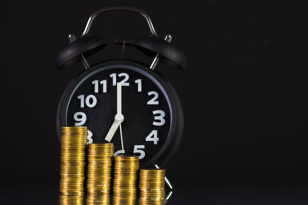 Coins stacks and alarm clock