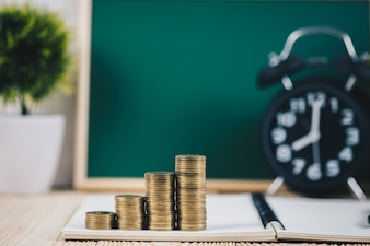 Coins stacks and alarm clock with green chalkboard