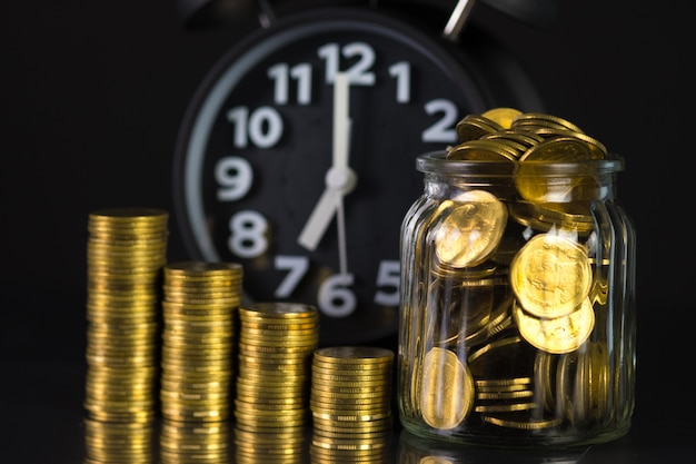 Coins stacks with coin in glass jar bottle and alarm clock
