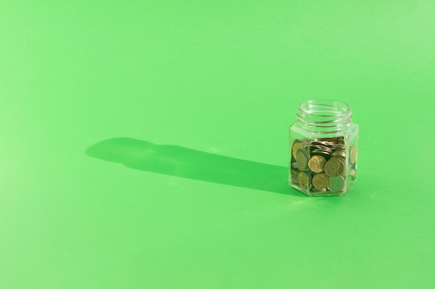 Coins in transparent glass jar on green background