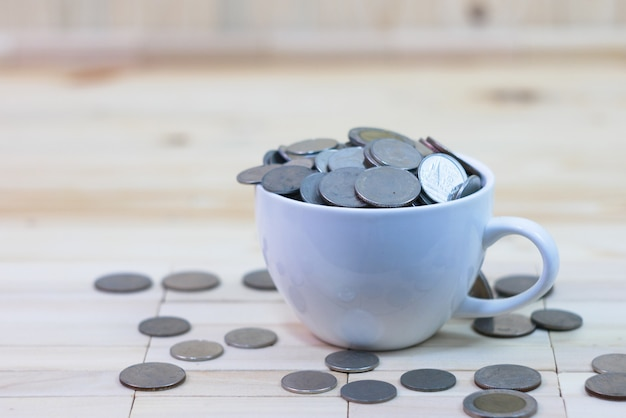 Coins in a white coffee cup is placed on a wooden table and around a cup