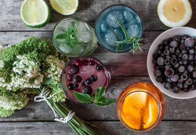 Coktail gin tonic, mojito и aperol spritz с мятой, льдом, лаймом, ягодами, грейпфрутом и апельсином на деревянном фоне.