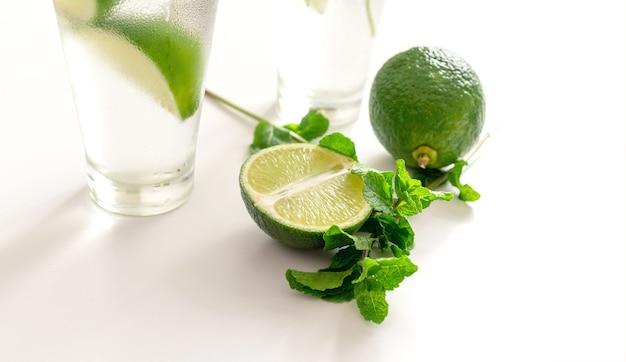Коктейль джин тоник или мохито в стакане с мятой, льдом, лаймом на белом фоне.