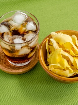 Cola and durian chips fried snack fruit in brown blow on green background