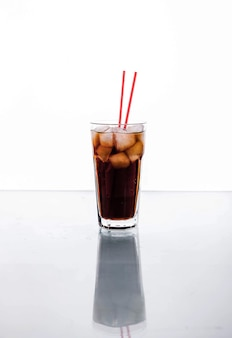 Cola in a glass with ice with red tube. soft drinks