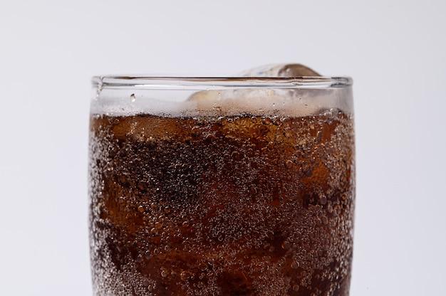 Кола в стакане с прозрачными кубиками льда, изолированные на белом фоне