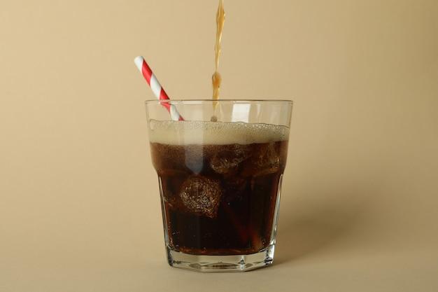 コーラはベージュの表面のガラスに注がれています