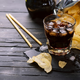 Cola with ice cubes in a glass and potato chips