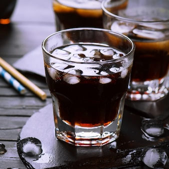 Cola with ice cubes in glasses on dark wooden table