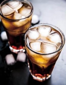 木製のテーブルの上に氷とコーラ。ソフトドリンク