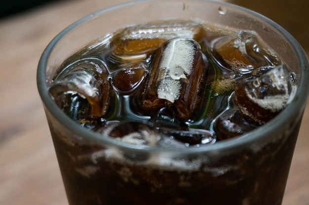 Cola with ice on table.