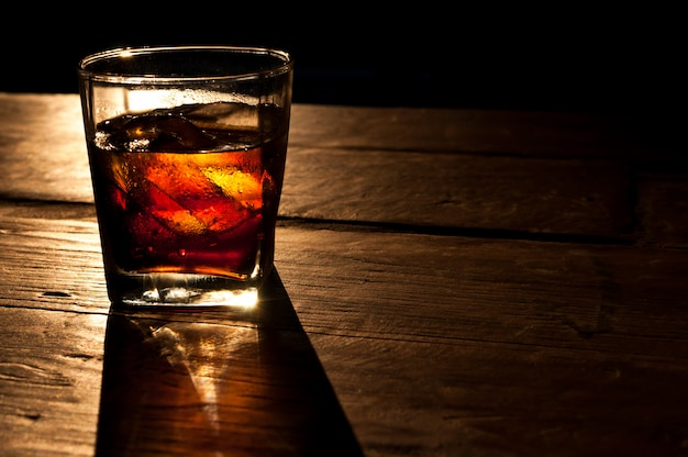 Cola with whiskey and ice on a wooden table background