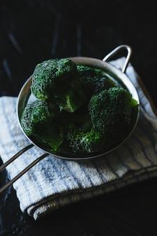 Colander of broccoli florets on black background.