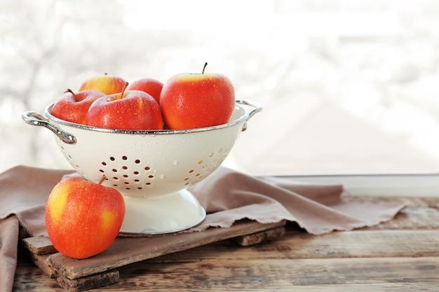Дуршлаг со свежими яблоками на подоконнике