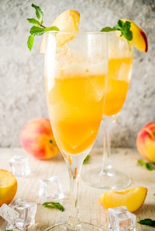 Cold alcohol beverage, iced peach bellini cocktail with mint leaves