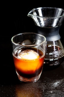 Cold americano decoration with ice ball in whisky glass on a black table.