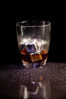 Холодное украшение американо с кубиками льда из нержавеющей стали на черном столе.