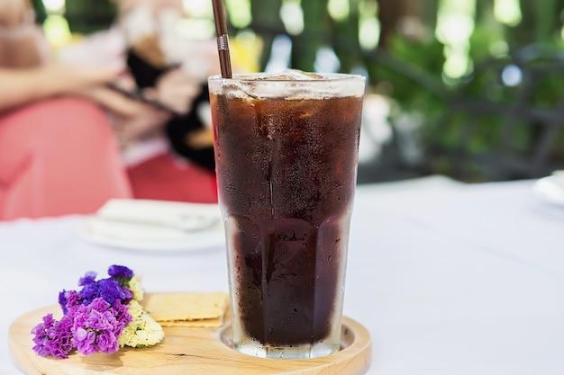 흰 천으로 커버 테이블에 차가운 아메리카노 유리-차가운 휴식 음료 개념