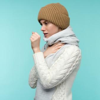 감기와 독감. 기침과 목이 아픈 느낌이 실내에서 아름 다운 젊은 여성의 초상화. 스카프 기침에 아픈 건강에 해로운 여자의 근접 촬영