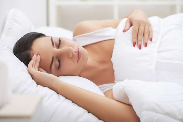 Простуда и грипп. женщина спит и держит голову при подсознательном стрессе или других возможных симптомах
