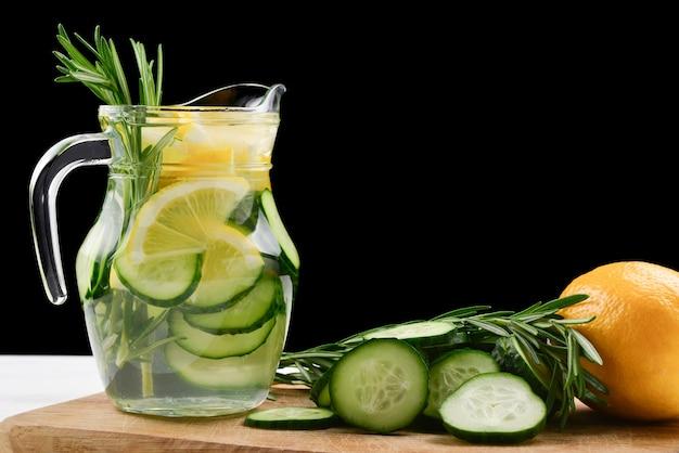 Холодная освежающая вода для детоксикации с лимоном, огурцом, розмарином и льдом в стеклянной банке