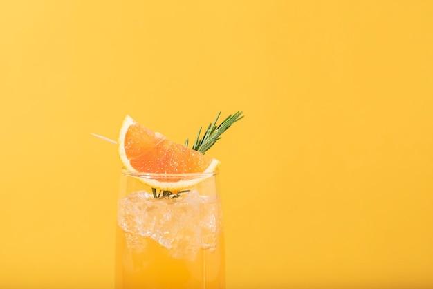 노란색 배경에 오렌지 슬라이스를 넣은 차갑고 상쾌한 오렌지 펀치 칵테일. 여름 음료.