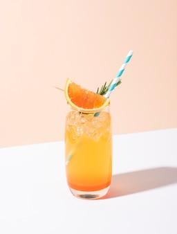 Холодный и освежающий апельсиновый коктейль пунш с долькой апельсина на желтом фоне. летний напиток.