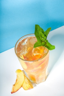 Холодный и освежающий летний напиток. классический коктейль из персикового чая со льдом